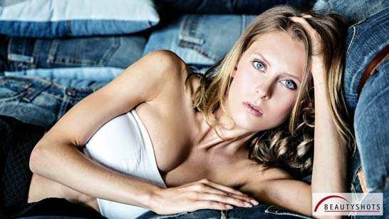 Foto von einer Frau liegend auf einem Sofa, die direkt in die Augen des Fotograf beim Beauty-Fotoshooting schaut