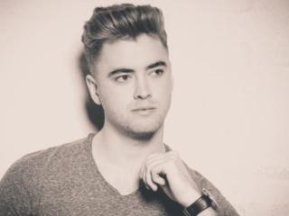 Sepiafoto von einem jungen Mann, der seine Uhr zeigt und nicht direkt in die Kamera schaut |Fotograf Hamburg Beautyshots Fotostudio