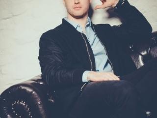 Foto von einem jungen Mann, der auf eine Couch sitzt mit der Hand am Kopf | Fotograf Beautyshots Fotostudio Hamburg