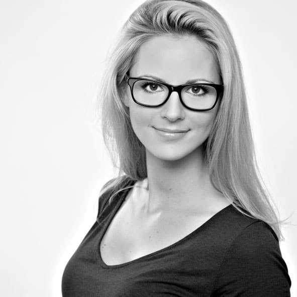 Business-Foto in schwarz-weiß von einer Frau mit Brille stehend, fotografiert während eines Business-Fotoshooting beim BEAUTYSHOTS Fotostudio in Hamburg