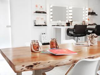 Foto von dem Make-up & Hairstyling-Bereich mit Holztisch im Vordergrund
