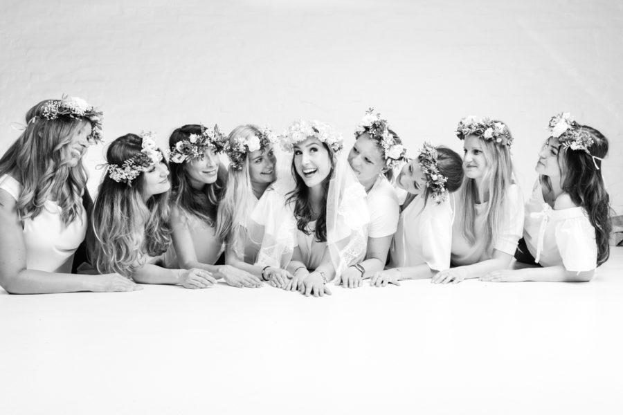 Schwarzweiß-Foto von einer JGA-Gruppe liegend auf dem Boden bei einem Junggesellinnen-Fotoshooting beim Beautyshots Fotostudio in Hamburg